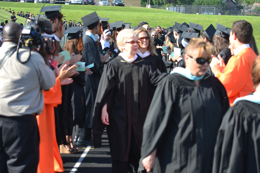 Description of . Teachers file through the two columns students formed on the track at the start of the graduation ceremony. Administrators, led by Principal Chuck Baughman, and school district officials also walked between the students. (Photo by Joe Slezak)