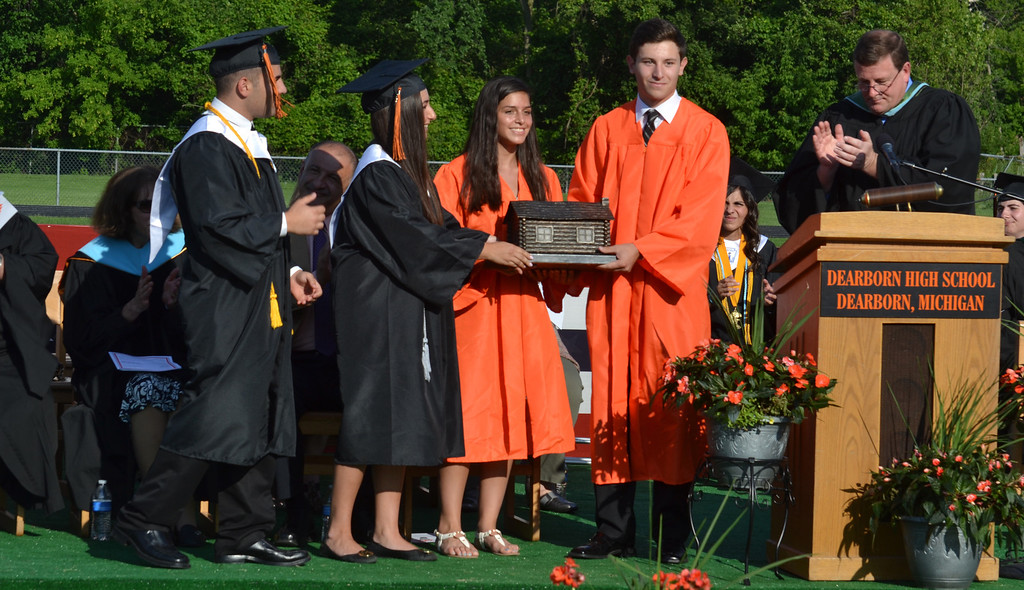 Description of . Leaders of Dearborn High School's senior class present a log cabin to leaders of the junior class. The tradition started in 1931. It represents present-day Dearborn's first school, which opened in 1835 in a log cabin. (Photo by Joe Slezak)
